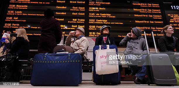 Passengers sit underneath an electronic information board showing cancelled and delayed trains at Kings Cross train station in London on December 21...