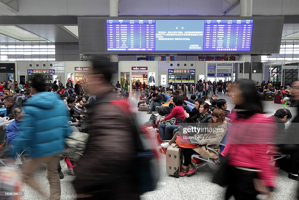 Passengers sit with their luggage as they wait to board trains at Hongqiao Railway Station in Shanghai, China, on Sunday, Feb. 3, 2013. Forecasts of snow and rain across China threaten to disrupt the travel plans of millions of Chinese heading home for the Lunar New Year holidays that start Feb. 9, the national weather agency warned. Photographer: Tomohiro Ohsumi/Bloomberg via Getty Images