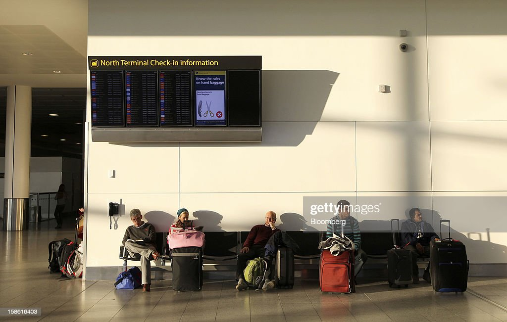 Passengers sit with their luggage beneath an electronic flight information screen in the check-in area of the north terminal at Gatwick airport in Crawley, U.K., on Friday, Dec. 21, 2012. U.K. airports predicted today to be the busiest day during the Christmas period, as some Britons opt to spend the holidays abroad and overseas visitors fly out to be with friends and family. Photographer: Chris Ratcliffe/Bloomberg via Getty Images