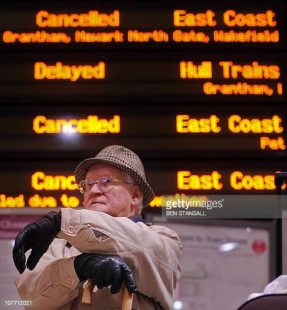 A passengers sits underneath an electronic information board showing cancelled and delayed trains at Kings Cross train station in London on December...