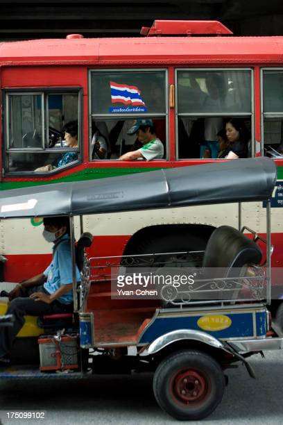 Passengers sleep in a bus stuck in a traffic jam on Sathorn Road in Bangkok An empty tuktuk is seen in the foreground