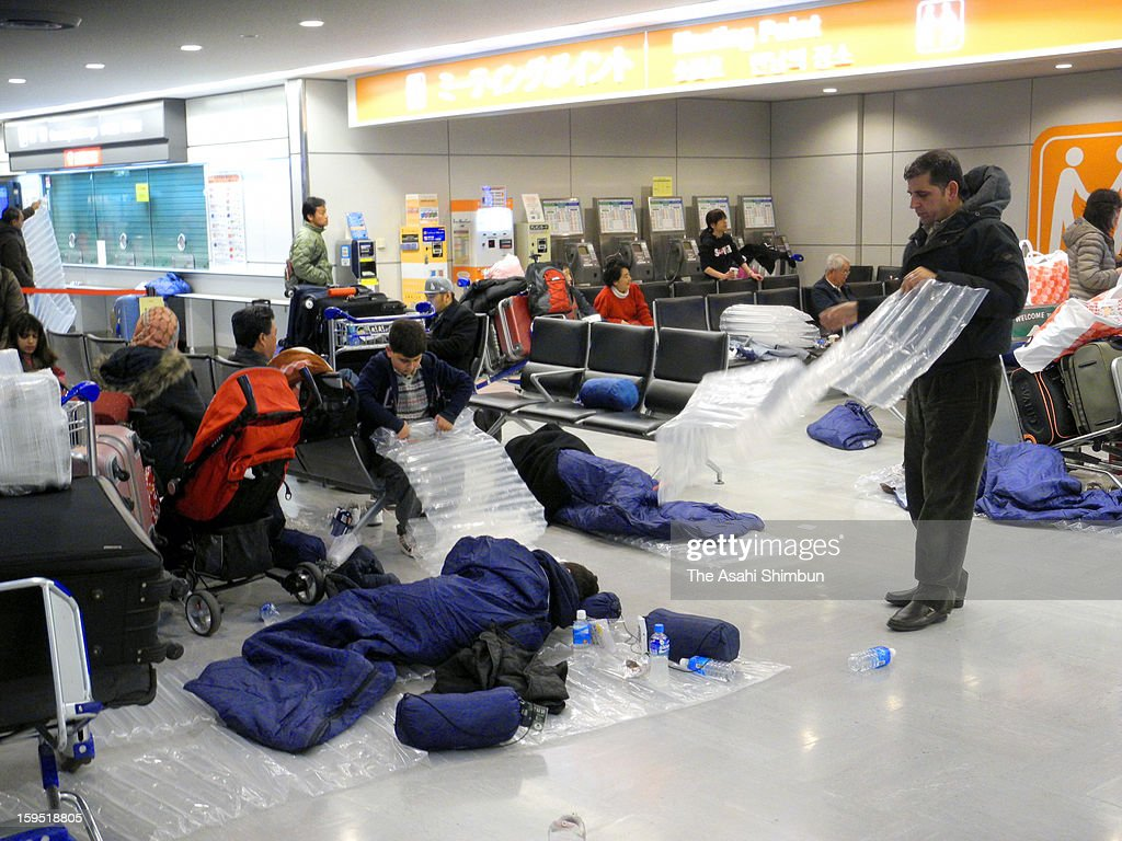 Passengers sleep in the sleeping bags provided by the airline companies due to the flights were cancelled due to the heavy snow and strong wind at Narita International Airport on January 15, 2013 in Narita, Chiba, Japan. A strong low pressure system caused heavy snow and strong wind in the coast area including Tokyo, more than 500 injured.
