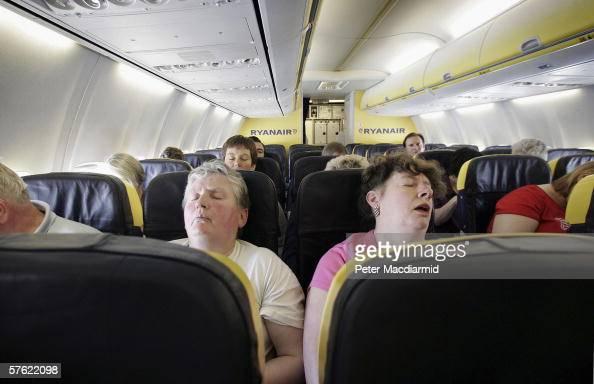 Passengers sleep on a low cost flight to Dinard in France on May 15 2006 from London Low cost airlines are increasing their market share in Europe by...