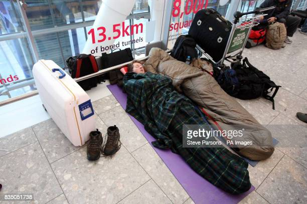 Passengers sleep on the floor of Terminal 5 at Heathrow Airport after nearly 800 flights were cancelled at the airport yesterday due to heavy...