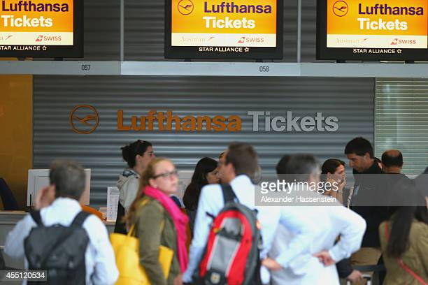 Passengers stand at a ticket counter of German airliner Lufthansa during a strike by Lufthansa pilots at Munich Airport on September 10 2014 in...