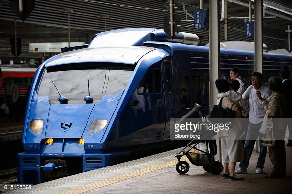 Passengers stand in front of a Kyushu Railway Co 883 series Sonic limited express service train at Hakata Station in Fukuoka Fukuoka Prefecture Japan...