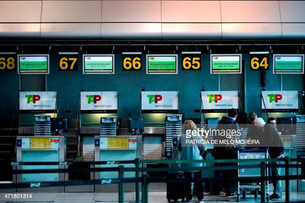 Passengers stand in front of TAP airline's checkin desks at Lisbon's Airport during a pilots strike on May 1 2015 Portuguese stateowned airline TAP...