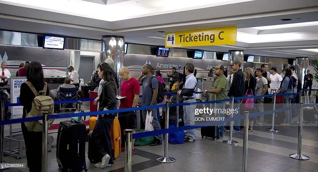 Passengers stand in line at LaGuardia Airport August 29 2011 in New York New Yorkarea airports reopened on Monday as US airlines gradually restored...