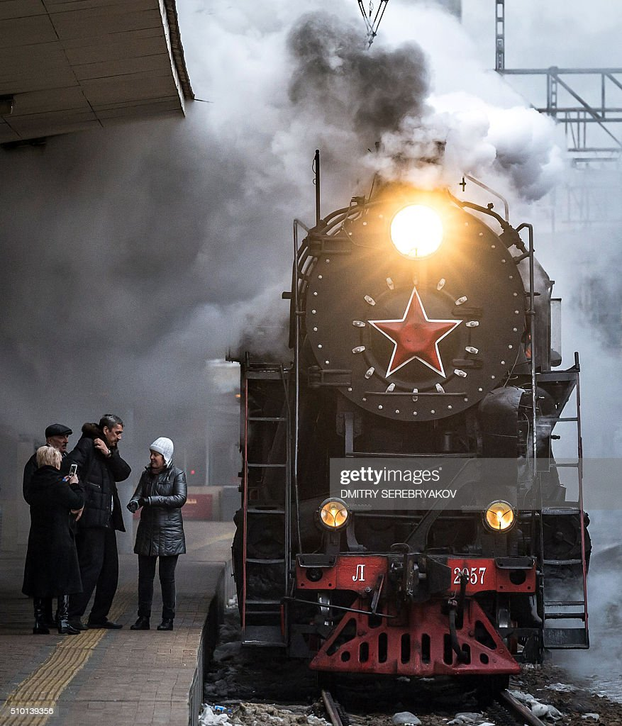 Passengers stand next to a steam locomotive to take part in a tourist journey at the Kursk railway station in Moscow early morning on February 14, 2016. / AFP / DMITRY SEREBRYAKOV