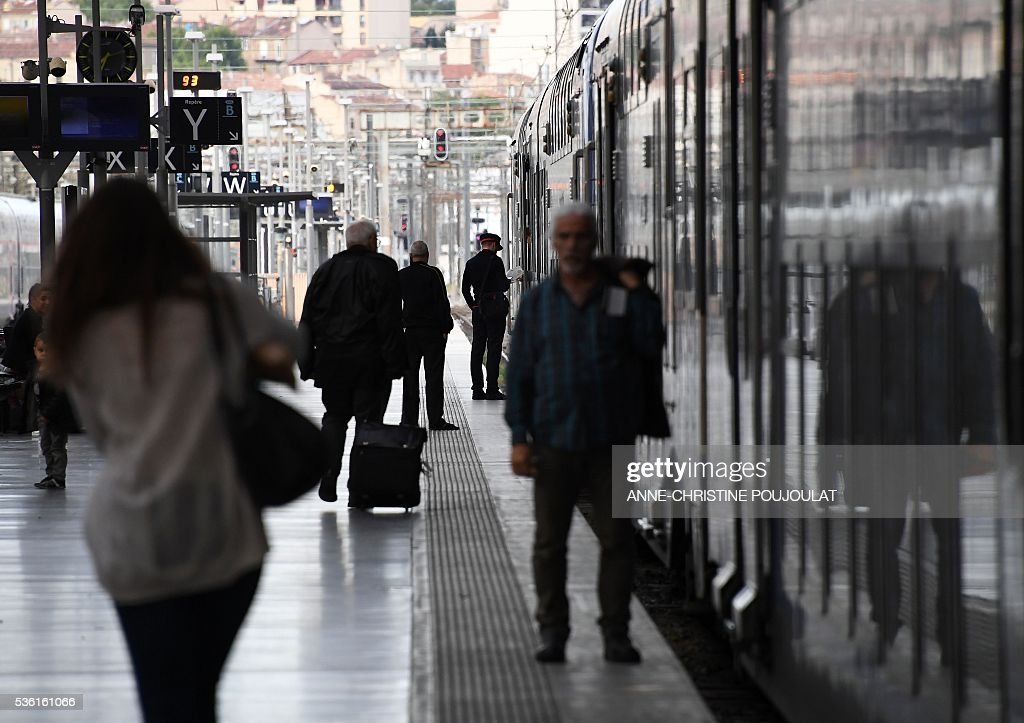 Passengers stand on a platform in the Saint-Charles rail station in Marseille, southeastern France, on May 31, 2016, at the start of a strike by employees of French state-owned rail operator SNCF to protest against government labour reforms. France is bracing for a week of severe disruption to transport after unions called for more action in their bitter standoff with the Socialist government over its labour market reforms. / AFP / ANNE