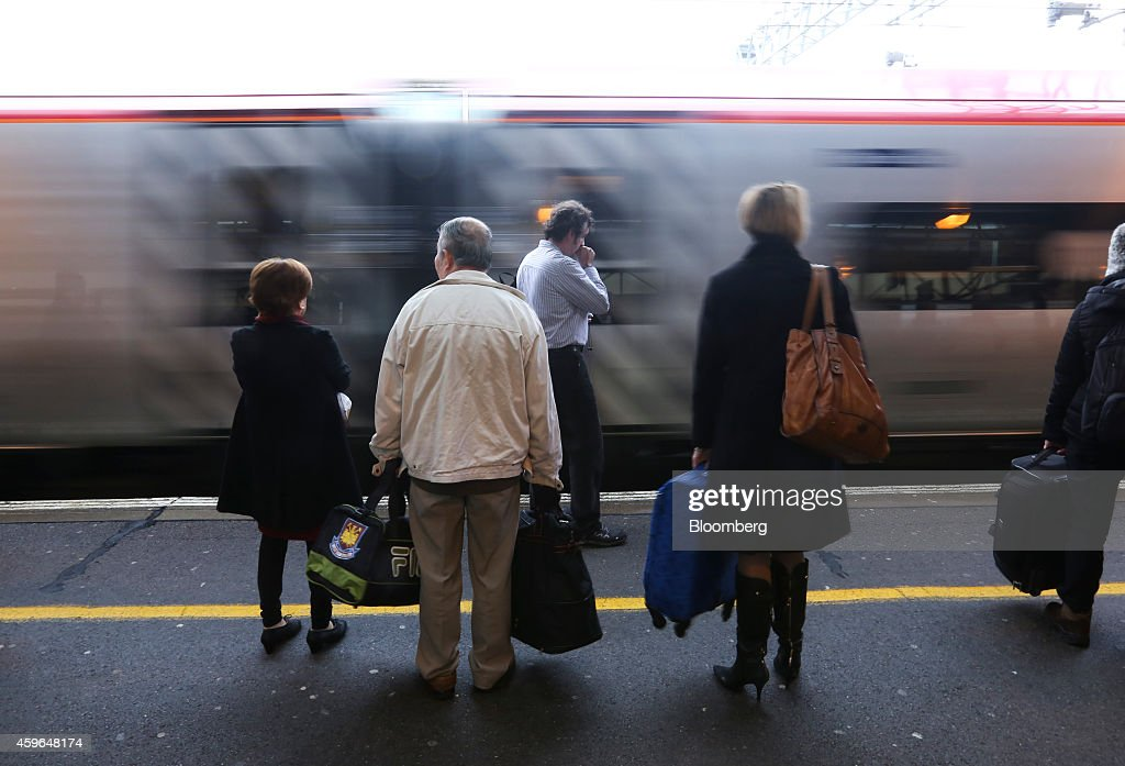 Passengers stand with luggage as a West Coast train, operated by Virgin Trains, arrives beside a platform at Milton Keynes railway station in Milton Keynes, U.K., on Thursday, Nov. 27, 2014. Virgin Trains and partner Stagecoach Group Plc were chosen to run the London-Edinburgh rail route, fending off rival bids from FirstGroup Plc and Eurostar International Ltd. and delivering a boost for Richard Branson a month after the fatal crash involving his space venture. Photographer: Chris Ratcliffe/Bloomberg via Getty Images