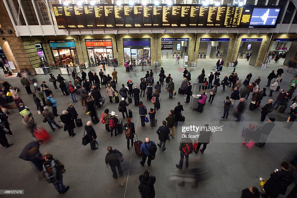 Passengers study the departure boards as they wait for trains in Kings Cross Station on December 23, 2013 in London, England. With two days until Christmas day, heavy rain and strong winds are affecting much of Southern England with numerous Met office weather warnings in place. Road, rail and ferry routes have been affected by the weather with gusts of wind and flooding anticipated in some areas.