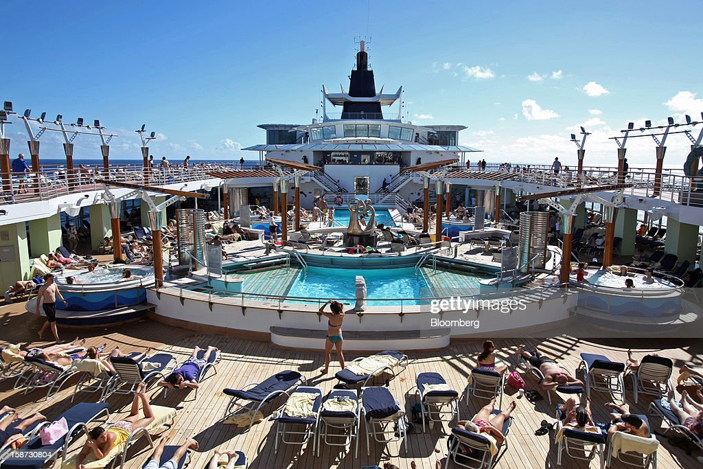 Passengers sunbathe and sit in Jacuzzis around the pool aboard Celebrity Cruises Inc.'s Constellation cruise ship in the Caribbean Sea near the coast of Cuba on Sunday, Dec. 16, 2012. Royal Caribbean Cruises Ltd. is a global cruise vacation company that operates Azamara Club Cruises, Celebrity Cruises, CDF Croisieres de France, Pullmantur Cruises and Royal Caribbean International. Photographer: Tim Boyle/Bloomberg via Getty Images