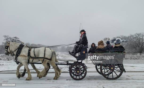 Passengers take a horse and carriage ride through heavy snow in Richmond Park on December 10 2017 in London England Heavy snow has hit many parts of...