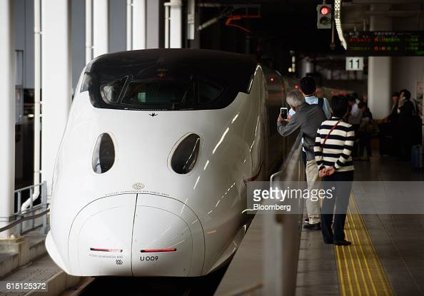 Passengers take photographs of a Kyushu Railway Co 800 series Shinkansen bullet train at Hakata Station in Fukuoka Fukuoka Prefecture Japan on...