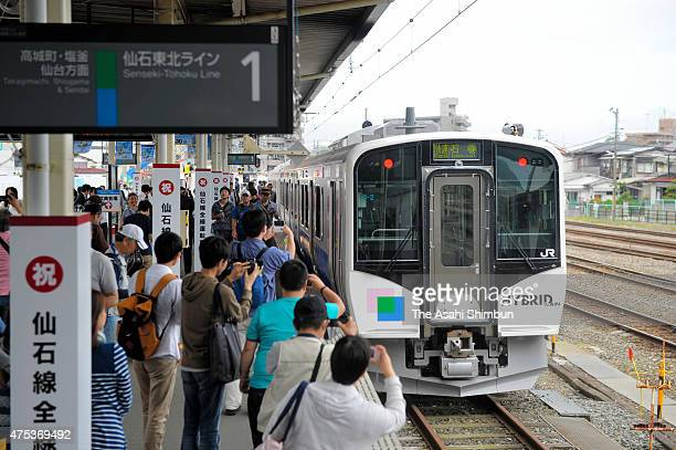 Passengers take photographs of the first train of JR Senseki Line at Ishinomaki Station on May 30 2015 in Ishinomaki Miyagi Japan After a more than...