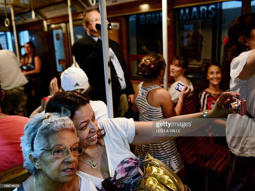 Passengers take snapshots inside a Le Burgeoise wagon of the A Line subway, in Buenos Aires, on January 11, 2013 during the so called last ride of the historic trains. The Line A will be closed betwen January 12 and March 8 following a decision by Buenos Aires city Mayor Mauricio Macri to replace the fleet with Chinese-made wagons. Line A was the first subway line to work in the southern hemisphere and its trains are among the ten oldest still working daily. The La Brugeoise wagons were constructed between 1912 and 1919 by La Brugeoise et Nicaise et Delcuve in Belgium. AFP PHOTO/Leo La Valle