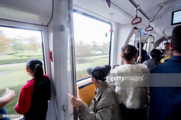 Passengers take the autonomousrail train during its test run on October 23 2017 in Zhuzhou Hunan Province of China The threecarriage railless train...