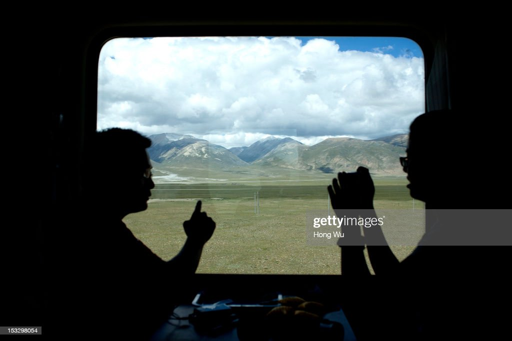 Passengers talk in a train carriage of from Beijing to Lhasa on August 15, 2012 in Damxung, China. After Qinghai-Tibet Railway went into operation on July 1, 2006, connecting China's capital Beijing and Lhasa of Tibet Autonomous Region by 4,064 km of railway line. Passengers and supplies are transported by train on this the world's highest railway to Tibet.