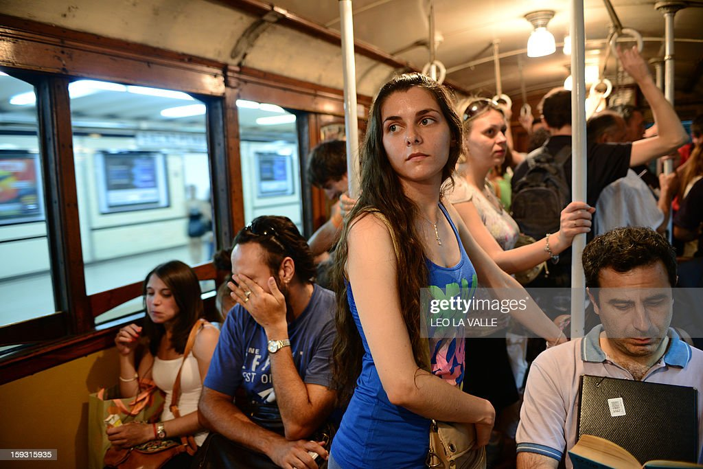 Passengers travel in one of the Le Burgeoise wagons of the A Line subway, in Buenos Aires, on January 11, 2013 during the so called last ride of the historic trains. The Line A will be closed betwen January 12 and March 8 following a decision by Buenos Aires city Mayor Mauricio Macri to replace the fleet with Chinese-made wagons. Line A was the first subway line to work in the southern hemisphere and its trains are among the ten oldest still working daily. The La Brugeoise wagons were constructed between 1912 and 1919 by La Brugeoise et Nicaise et Delcuve in Belgium. AFP PHOTO/Leo La Valle