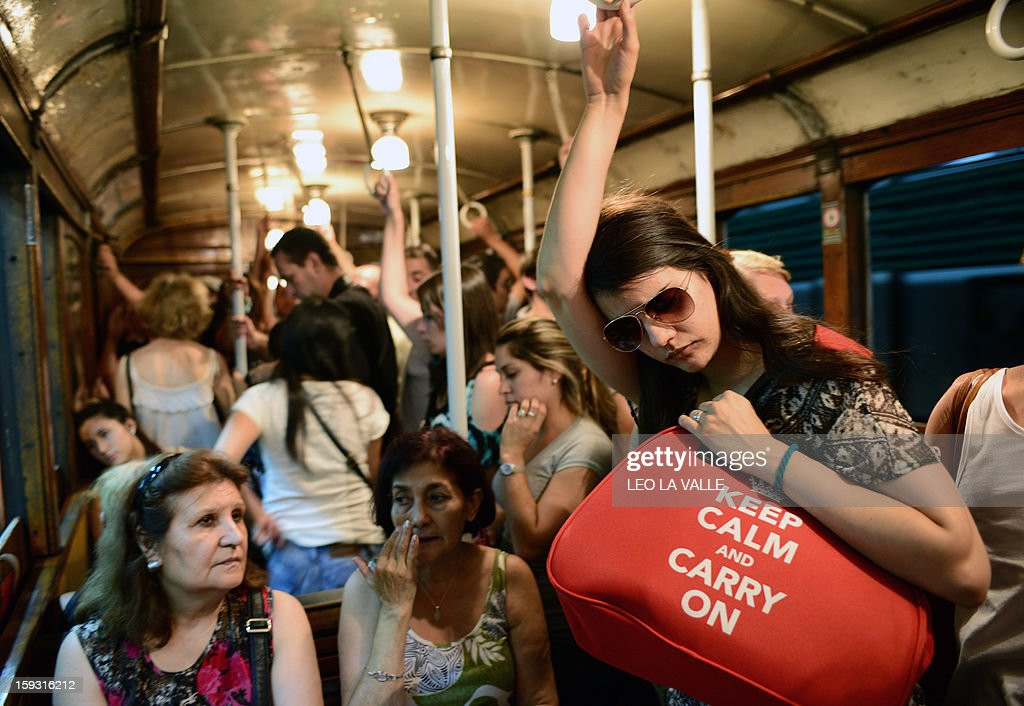 Passengers travel on a Le Burgeoise wagon of the A Line subway, in Buenos Aires, on January 11, 2013 during the so called last ride of the historic trains. The Line A will be closed betwen January 12 and March 8 following a decision by Buenos Aires city Mayor Mauricio Macri to replace the fleet with Chinese-made wagons. Line A was the first subway line to work in the southern hemisphere and its trains are among the ten oldest still working daily. The La Brugeoise wagons were constructed between 1912 and 1919 by La Brugeoise et Nicaise et Delcuve in Belgium. AFP PHOTO/Leo La Valle