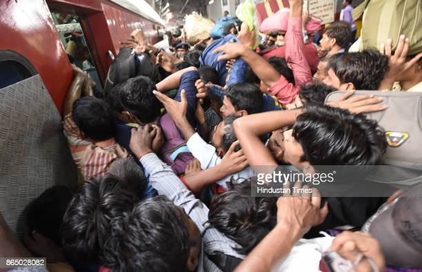 Passengers trying to board the stationed 12394 Sampoorn Kranti Express train which runs from New Delhi to Patna who wanted to go to their native...