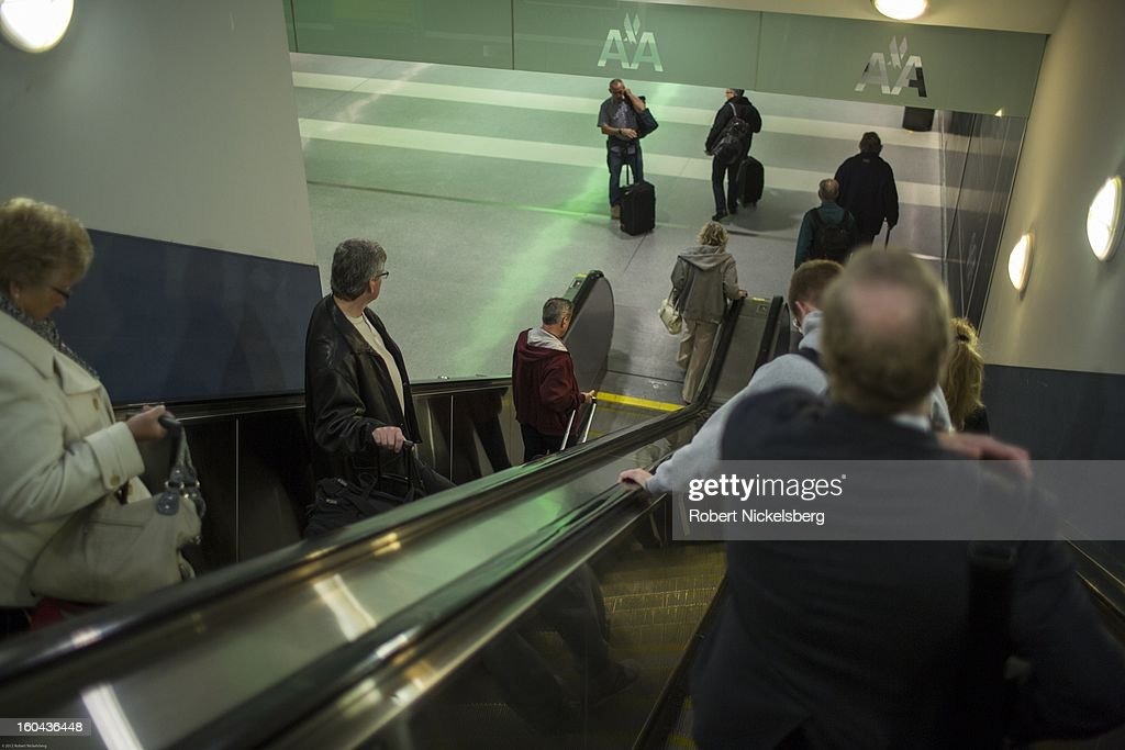 Passengers use an escalator to reach the American Airlines departure terminal January 28, 2013 at the LaGuardia Airport in the Queens borough of New York.