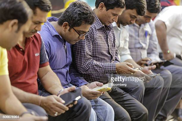 Passengers use smartphones at Mumbai Central railway station in Mumbai India on Friday Jan 22 2016 Google Inc in partnership with RailTel Corp and...
