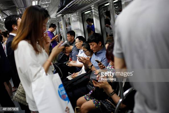 Passengers use smartphones inside a subway train in Seoul South Korea on Friday July 17 2015 A report on July 23 may show that South Korea's economy...