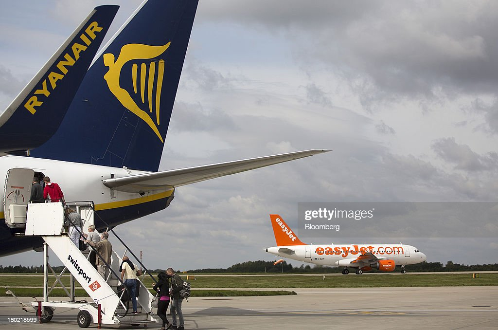 Passengers use the rear steps to board an aircraft operated by Ryanair Holdings Plc, as an EasyJet Plc aircraft departs from Stansted Airport, operated by Manchester Airports Group (MAG) in Stansted, U.K., on Tuesday, Sept. 10, 2013. From two planes in 1995, EasyJet has grown to more than 200 Airbus SAS aircraft carrying more than 59 million people annually, 20 million fewer than Ryanair. Photographer: Simon Dawson/Bloomberg via Getty Images