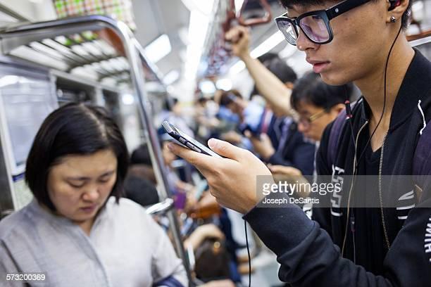Passengers using smartphones on a Seoul subway train South Korea