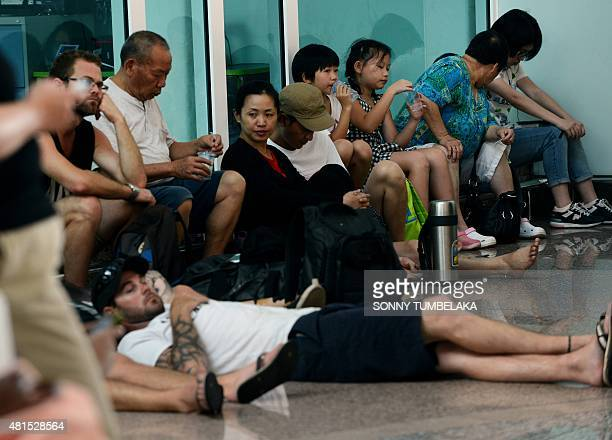 Passengers wait around for information about delayed flights at the international departure area of Bali's Ngurah Airport in Denpasar on July 22 2015...