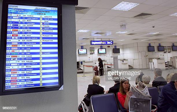 Passengers wait as a board informs about the traffic with planes delayed on May 9 2010 at the Nice international airport French Riviera three days...