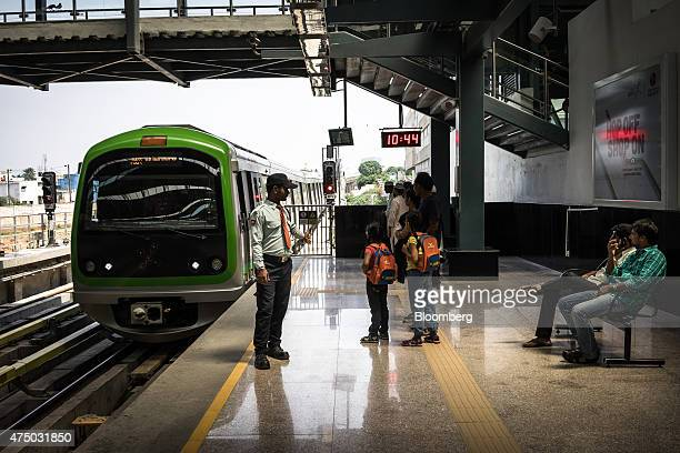 Passengers wait as a train arrives at Mantri Sampige Square Metro station operated by Bangalore Metro Rail Corp in Bengaluru India on Sunday May 3...