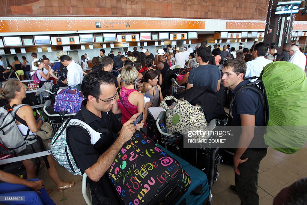 Passengers wait at a check-in desk, on January 2, 2013 at Gillot airport in Sainte-Marie de la Reunion, a French island located in the Indian Ocean, as the airport is to shut down as tropical storm Dumile is forecast to strike the island as a tropical cyclone later today.