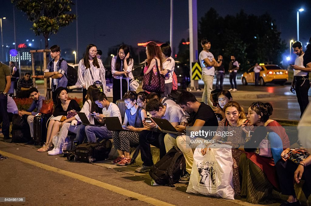 Passengers wait at Ataturk airport`s main enterance in Istanbul, on June 28, 2016, after two explosions followed by gunfire hit Turkey's largest airport, killing at least 10 people and injuring 20. All flights at Istanbul's Ataturk international airport were suspended on June 28, 2016 after a suicide attack left at least 36 people dead. / AFP / OZAN