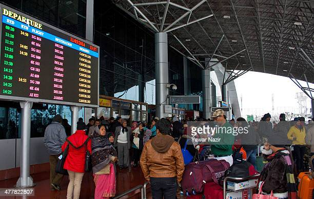 Passengers wait at the airport after all the flights were cancelled by the authorities following a heavy snowfall on March 11 in Srinagar the summer...