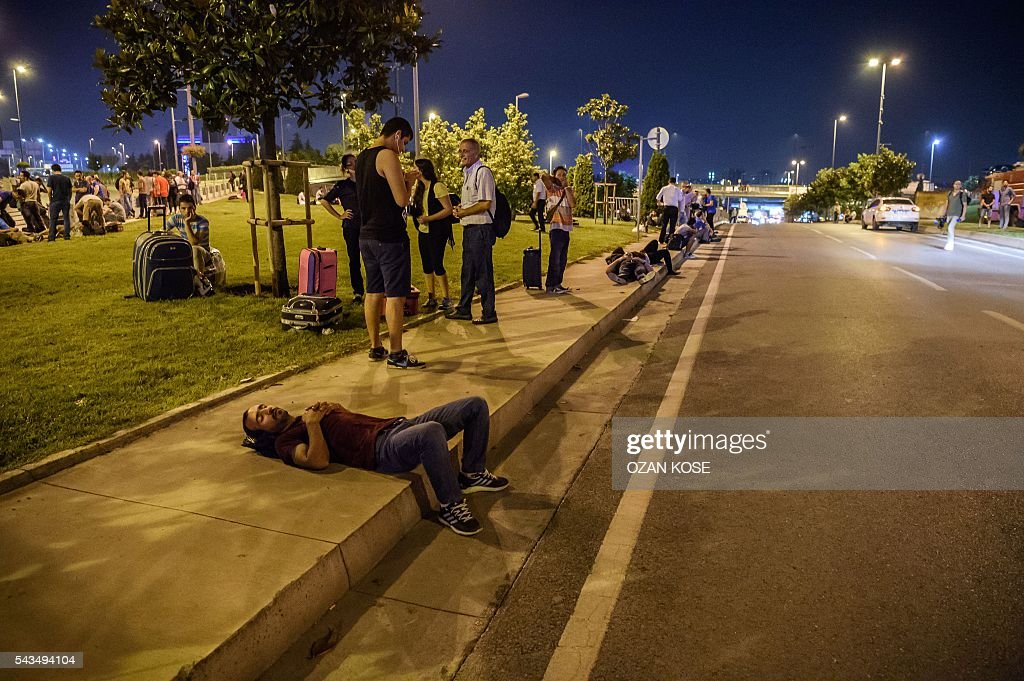 Passengers wait at the Ataturk airport`s main enterance in Istanbul, on June 28, 2016, after two explosions followed by gunfire hit Turkey's biggest airport, killing at least 28 people and injuring 20. All flights at Istanbul's Ataturk international airport were suspended on June 28, 2016 after a suicide attack left at least 10 people dead and 20 others wounded, Turkish television stations reported. / AFP / OZAN