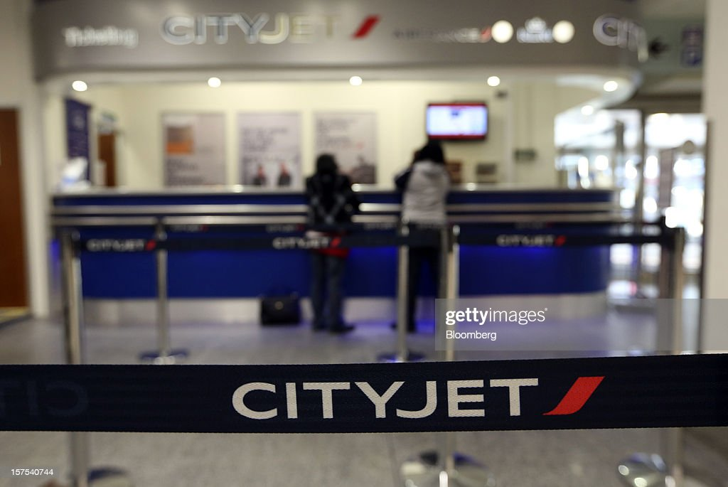 Passengers wait at the CityJet Ltd. information desk inside City Airport in London, U.K., on Tuesday, Dec. 4, 2012. Air France-KLM Group's CityJet unit is studying options for a new investor, with a trade buyer a possibility given its strength at London City airport, Chief Executive Officer Christine Ourmieres said in an interview. Photographer: Chris Ratcliffe/Bloomberg via Getty Images