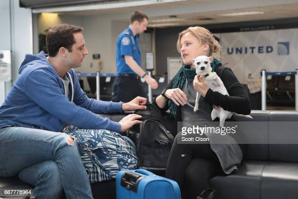 Passengers wait for a flight at the United Airlines terminal at O'Hare International Airport on April 12 2017 in Chicago Illinois United Airlines has...