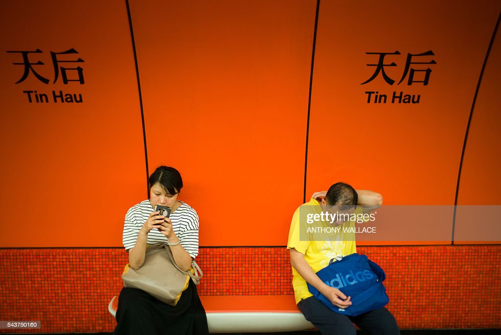Passengers wait for a MTR (Mass Transit Railway) train at Tin Hau station in Hong Kong on June 30, 2016. / AFP / ANTHONY