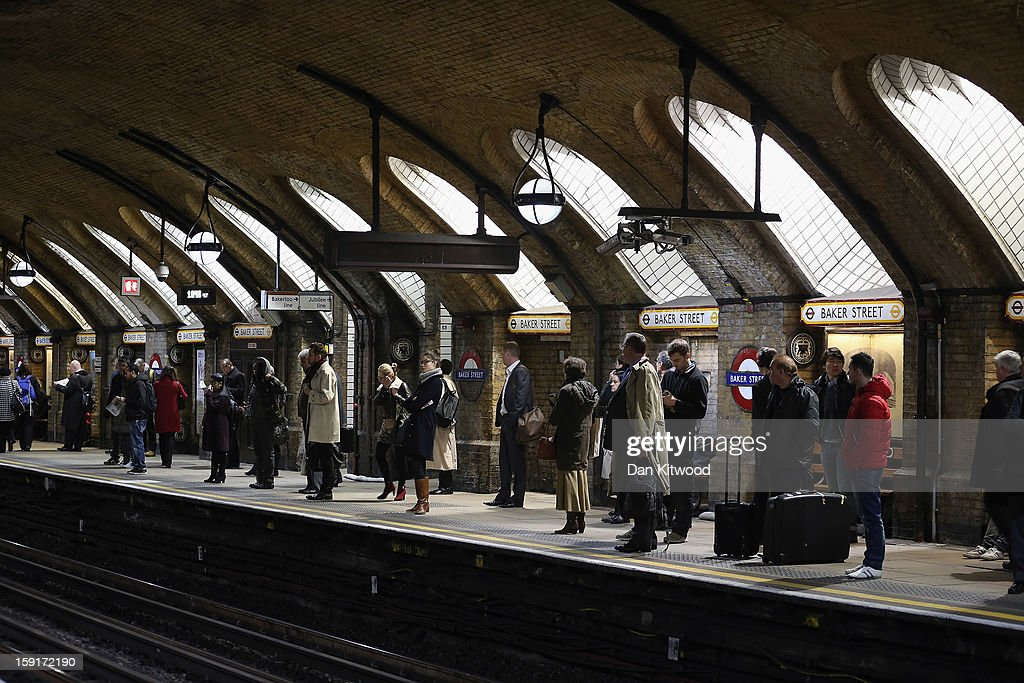 Passengers wait for a train at Baker Street Underground Station on January 9, 2013 in London, England. Baker Street Station shares the 150th Anniversary of its opening on January 10th, 2013 with the London Underground. Commonly called the Tube, the London Underground is the oldest of its kind in the world and now carries approximately a quarter of a million people around its network of 249 miles of track every day. Baker Street station was remodeled between 1911-13 by architect Charles W Clark to its present form as part of a comprehensive rebuilding project by the Metropolitan Railways with the station as its new company headquarters and flagship station, where it quickly became known as the 'Gateway to Metro - Land'. Outside the Marylebone Road exit, a large statue commemorates Sherlock Holmes, Sir Arthur Conan Doyles ficticious detective who resided in the novels at 221B Baker Street.