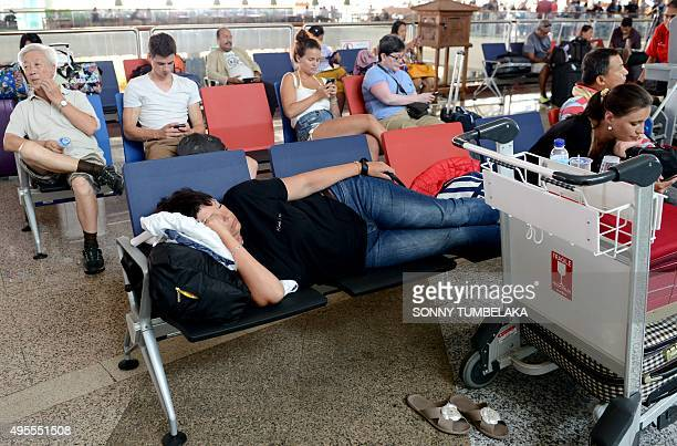 Passengers wait for information on delayed and cancelled flights at the international departure area of Bali's Ngurah Rai Airport in Denpasar on...