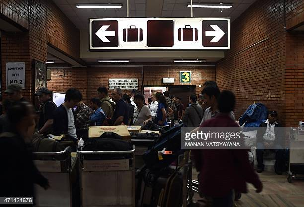 Passengers wait for luggage upon arrival at the main international airport in Kathmandu on April 28 2015 Hungry and desperate villagers rushed...