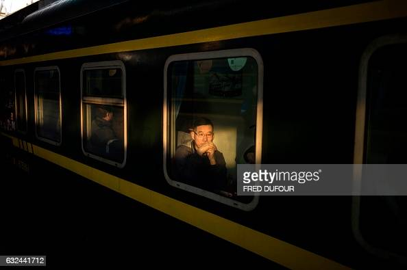 TOPSHOT Passengers wait for the departure of their train as they travel to their hometowns for the 'Spring Festival' or Lunar New Year on January 23...