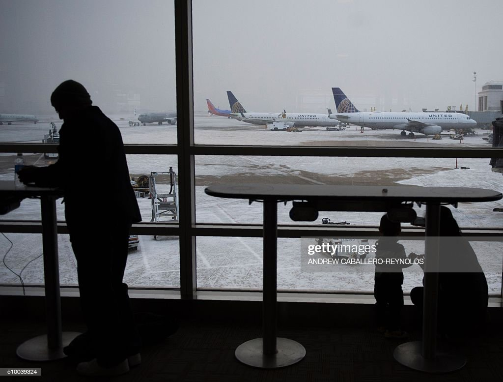 Passengers wait for their flight during a snow storm at Ronald Regan National Airport in Washington, DC, on February 13, 2016. / AFP / ANDREW CABALLERO-REYNOLDS