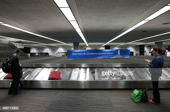 Passengers wait for their luggage at San Francisco International Airport on March 13 2015 in San Francisco California According to a passenger...