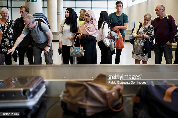 Passengers wait for their luggage next to the baggage carousel after landing with the first commercial flight at Castellon airport on September 15...