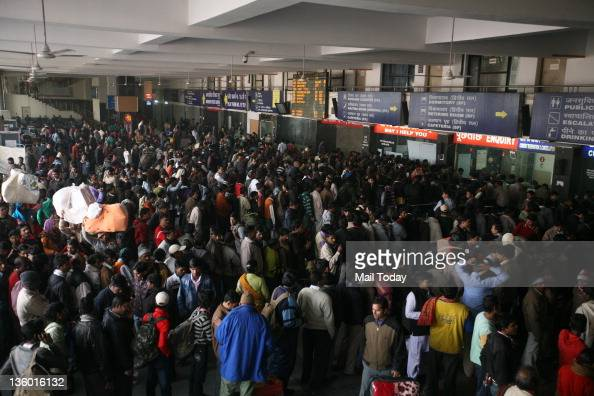 Passengers wait for their train at New Delhi Railway Station in the capital on Monday A thick fog disrupted road and rail traffic at several places...