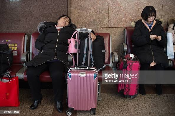 Passengers wait for their trains before travelling to their hometowns for the 'Spring Festival' or Lunar New Year on January 24 2017 at Beijing...